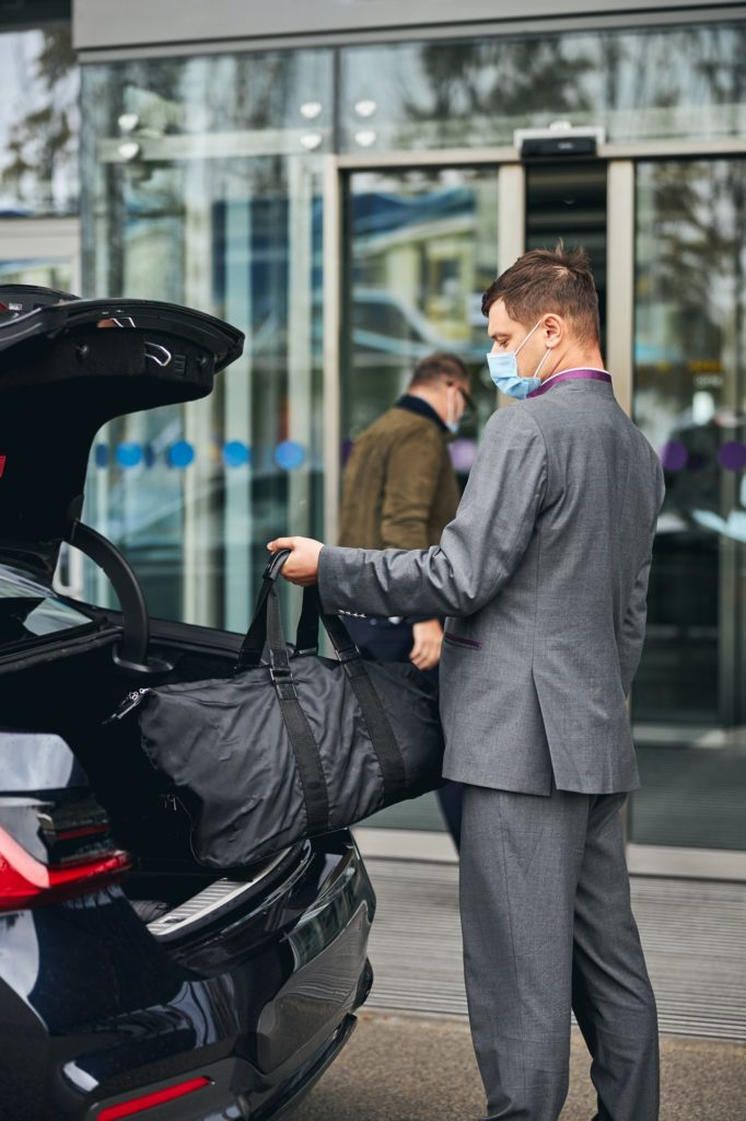 Driver helping his passenger with his luggage